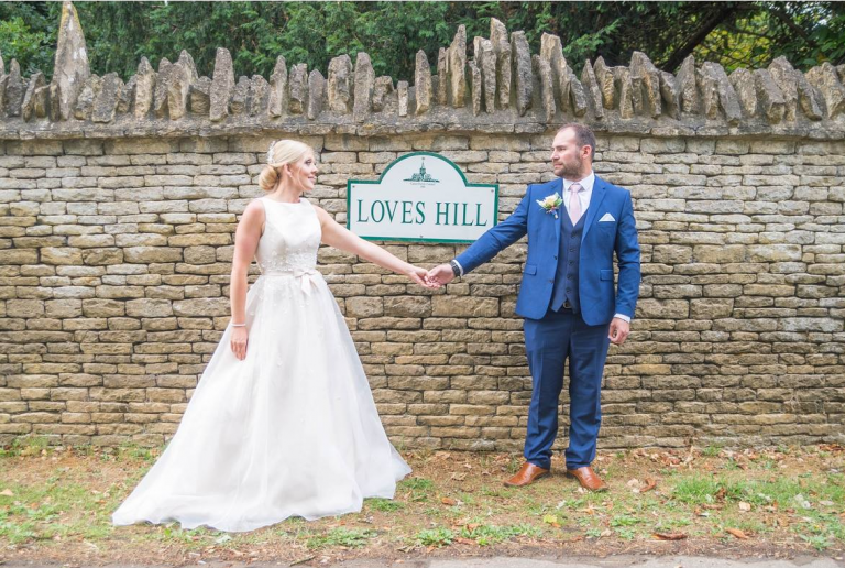 bride and groom with street sign saying love hill