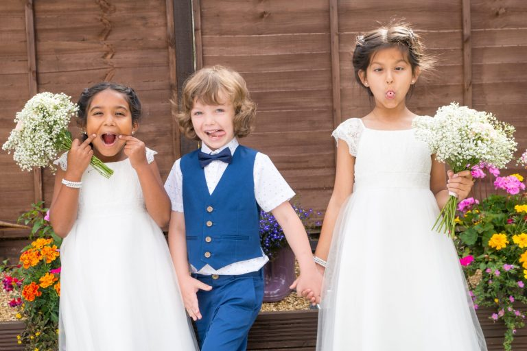 children pulling funny faces at a wedding